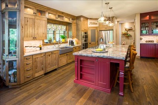Beautifully renovated kitchen from Lloyd's Cabinet Shop with wood cabinets and red island